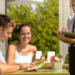 Couple at cafe ordering from menu with waitress